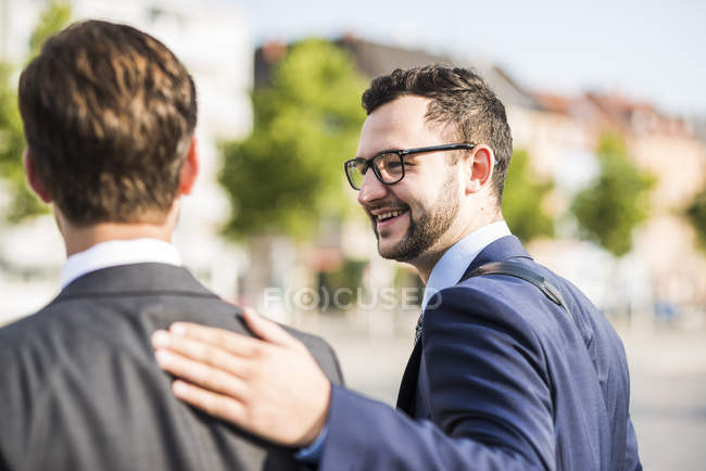 Two young businessmen walking in city, one patting colleagues back — Stock Photo