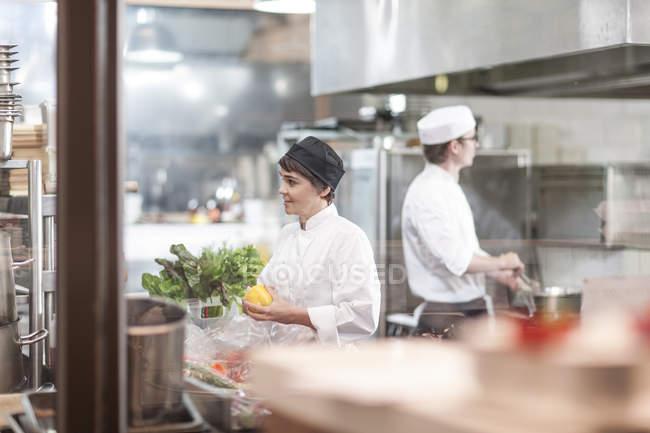 Dos ches preparando comida en la cocina del restaurante - foto de stock