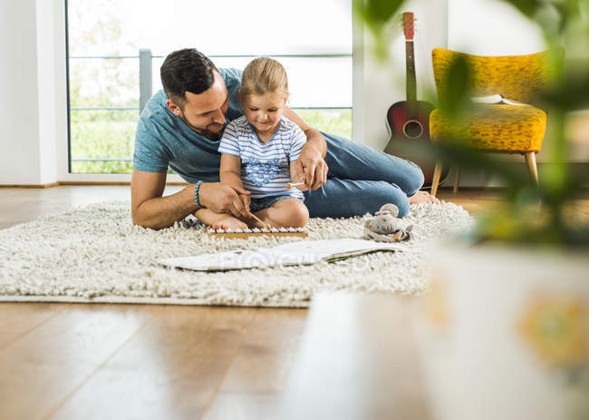 Father with daughter on rug playing glockenspiel — Stock Photo