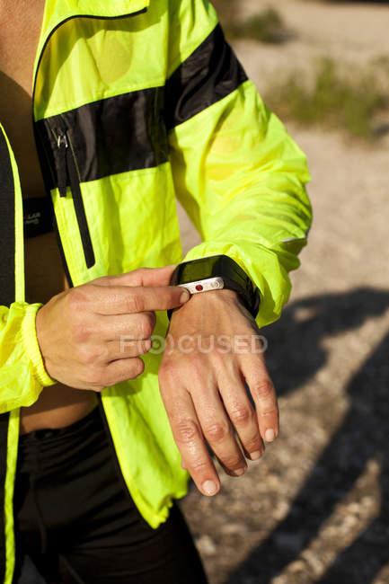 Человек в спортивную одежду, регулируя его smartwatch — стоковое фото