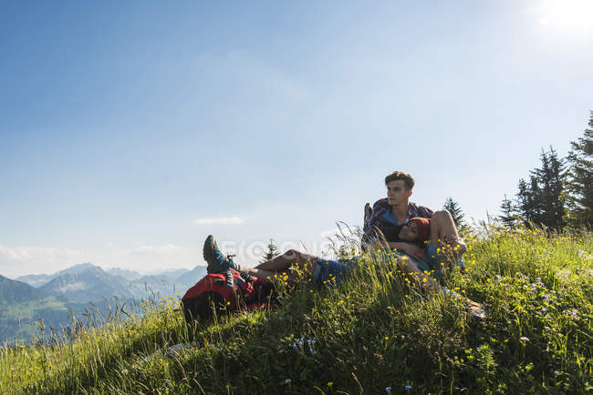 Austria, Tyrol, Tannheimer Tal, young couple resting on alpine meadow — Stock Photo