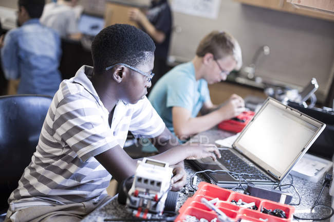 Écoliers de travail avec ordinateur portable en classe de robotique — Photo de stock