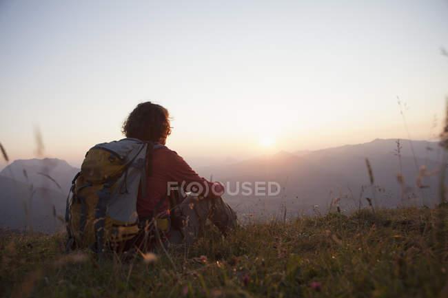Австрия, Тироль, Унтербергхорн, турист, отдыхающий на альпийском ландшафте на закате — стоковое фото