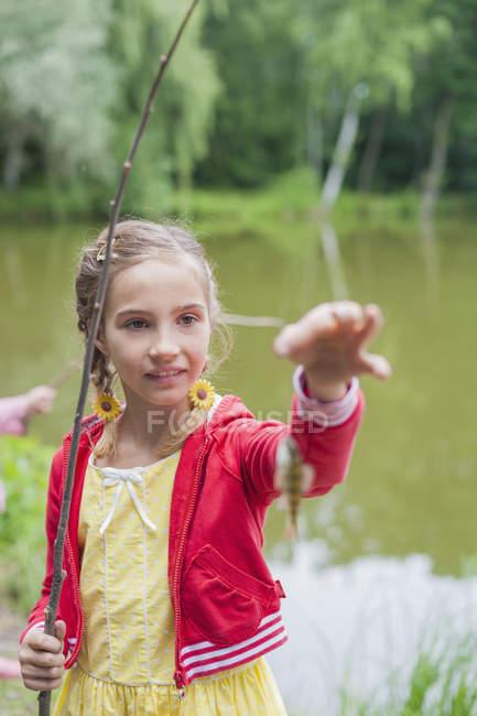 Chica con caña y peces pequeños - foto de stock