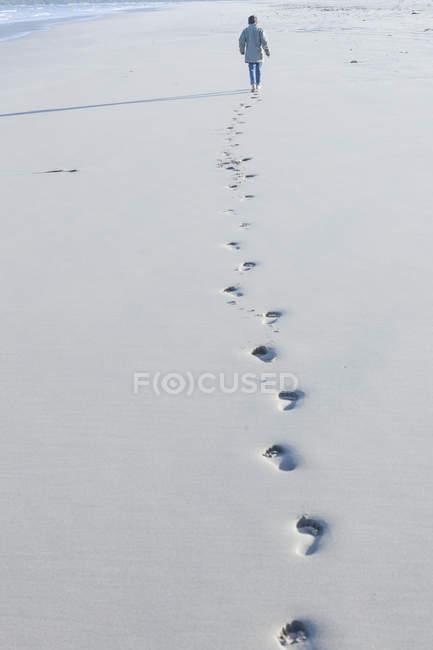 Vue arrière d'un garçon marchant sur la plage — Photo de stock