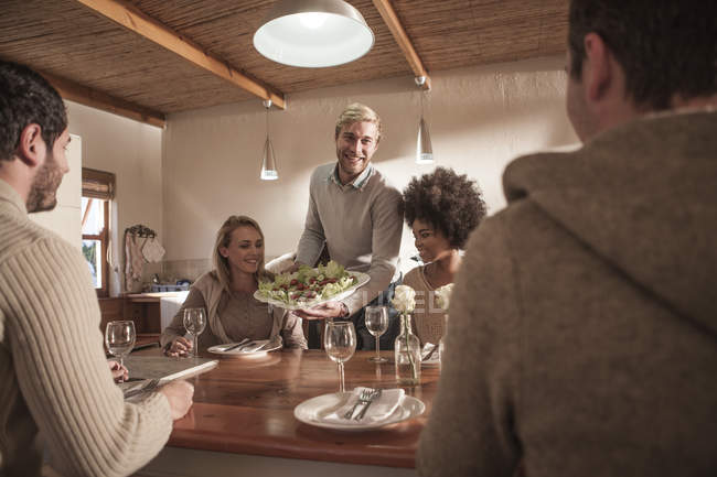 Young man serving plate with salad for friends — Stock Photo