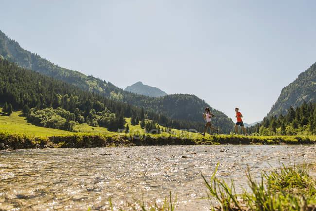 Austria, Tirol, Valle de Tannheim, pareja joven para correr en riverside - foto de stock