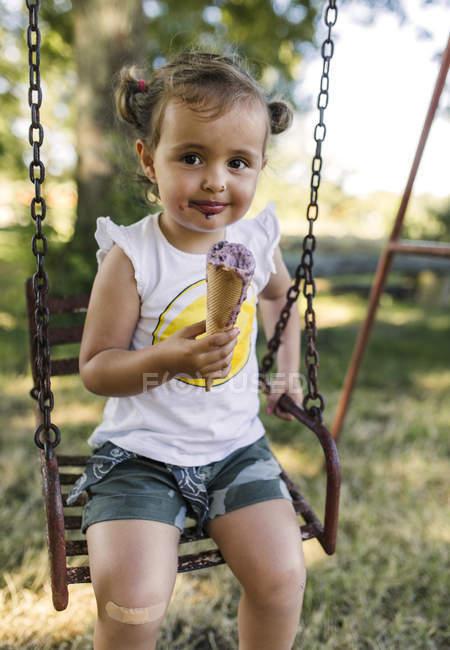 Retrato de una niña feliz sentada en un columpio comiendo helado - foto de stock