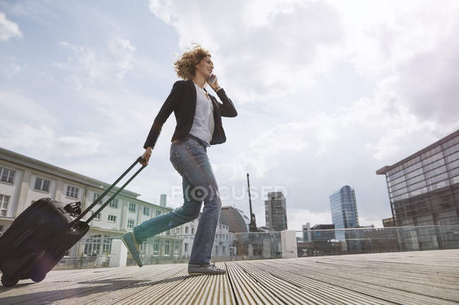 Woman on the phone walking with a rolling suitcase in the city — Stock Photo