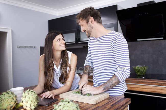 Lächelnde paar von Angesicht zu Angesicht ich ihre moderne Küche — Stockfoto