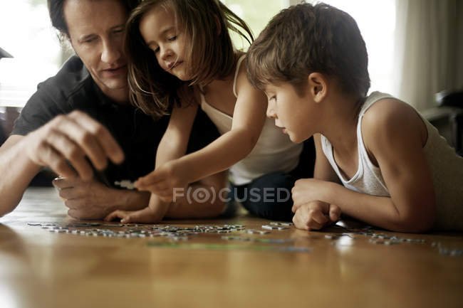 Father playing with children, lying on floor — Stock Photo