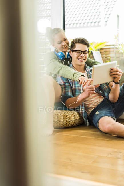 Щасливі молода пара вдома обміну цифровий планшетний — стокове фото