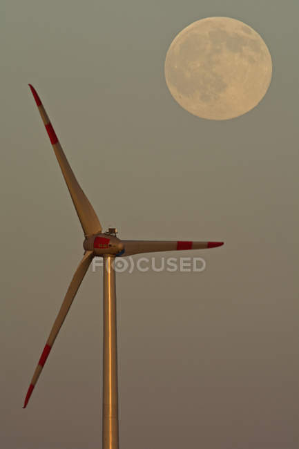 Deutschland, Vollmond in der Abenddämmerung mit Windrad im Vordergrund — Stockfoto