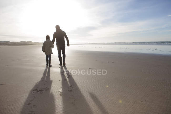 South Africa, Witsand, father and son walking on the beach at backlight — Stock Photo