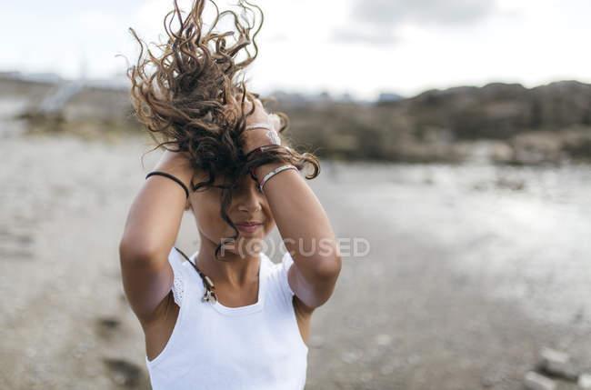 Petite fille sur la plage tenant ses cheveux soufflants — Photo de stock