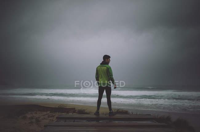 Visão traseira do corredor em pé no oceano em um clima tempestuoso — Fotografia de Stock