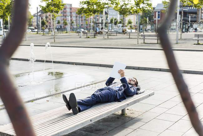 Jeune homme d'affaires allongé sur le banc, travaillant — Photo de stock