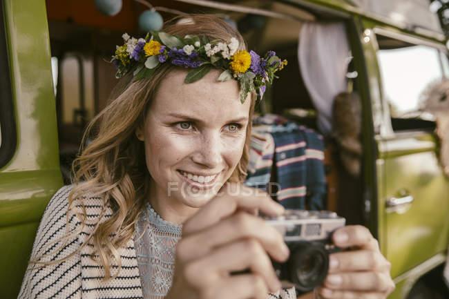 Женщина-хиппи с аналоговой камерой перед фургоном — стоковое фото