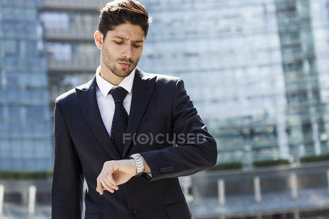 Portrait of young businessman checking the time — Stock Photo
