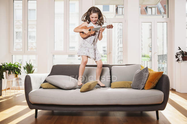 Happy girl playing mini guitar while jumping on a couch in living room at home — Stock Photo