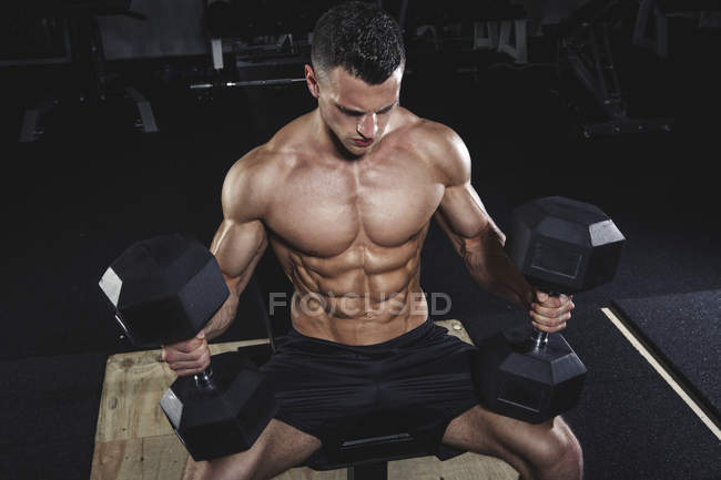 Physical athlete doing dumbbell bench presses in gym — Stock Photo