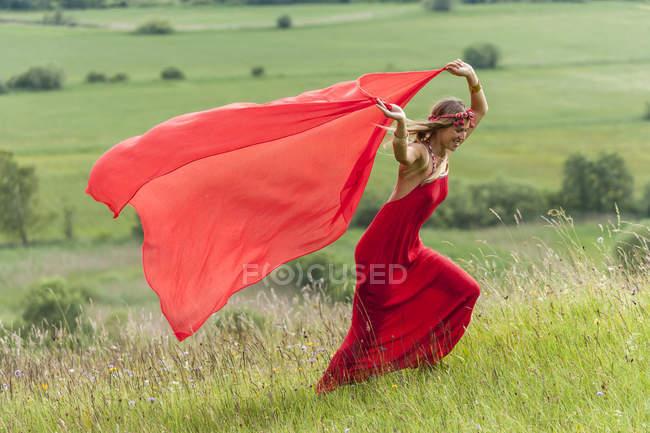 Жінка в червоній сукні, які працюють на луг червоною ганчіркою — стокове фото