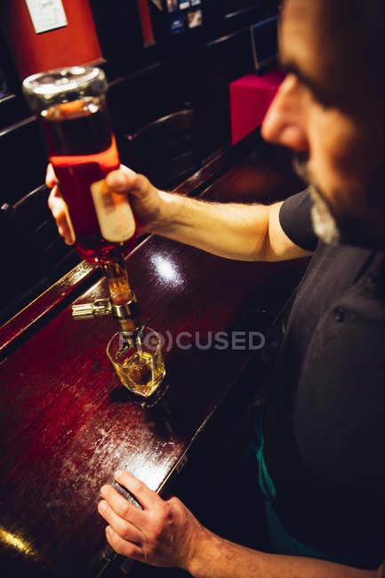 Официант наливает виски в ирландский паб — стоковое фото