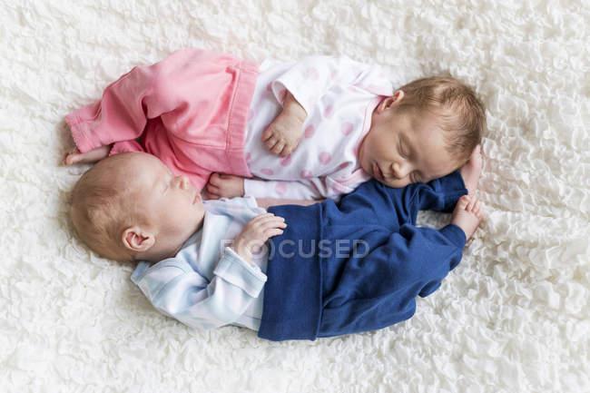 Новорожденных Близнецы сна голова toe на белом одеяле — стоковое фото