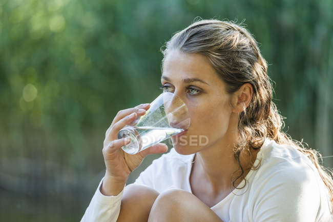 Beautiful woman with wet hair drinking glass of water — Stock Photo
