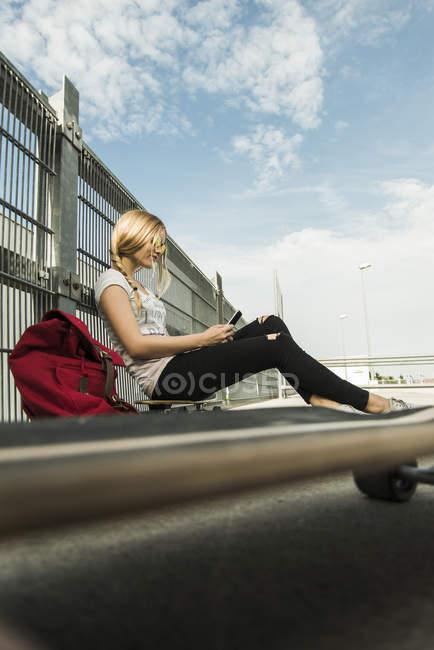 Adolescente, assis sur une planche à roulettes à l'aide de téléphone portable — Photo de stock