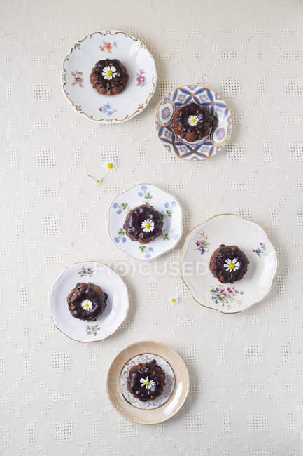 Vista elevata di mini torte al cioccolato con fiori commestibili su piastre — Foto stock