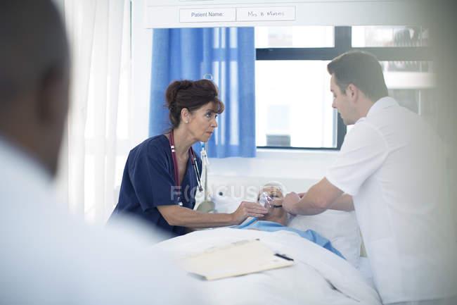 Arzt und Krankenschwester tragen Sauerstoffmaske auf Patient im Krankenhausbett auf — Stockfoto