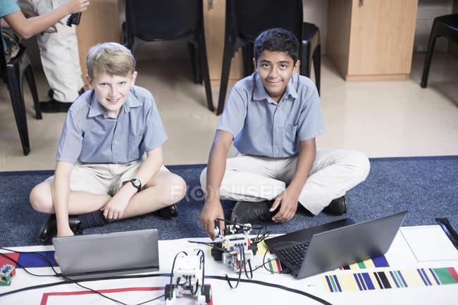 Retrato de dois meninos de escola sorridentes com laptops em aula de robótica — Fotografia de Stock