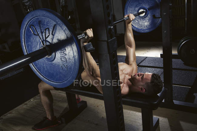 Physical athlete doing barbell bench presses in gym — Stock Photo
