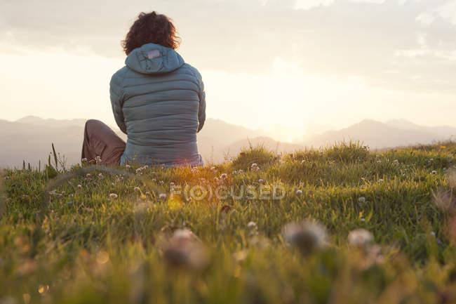 Austria, Tirol, Unterberghorn, caminante descansando en paisaje alpino al amanecer - foto de stock