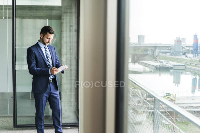 Young businessman at the window looking on digital tablet — Stock Photo