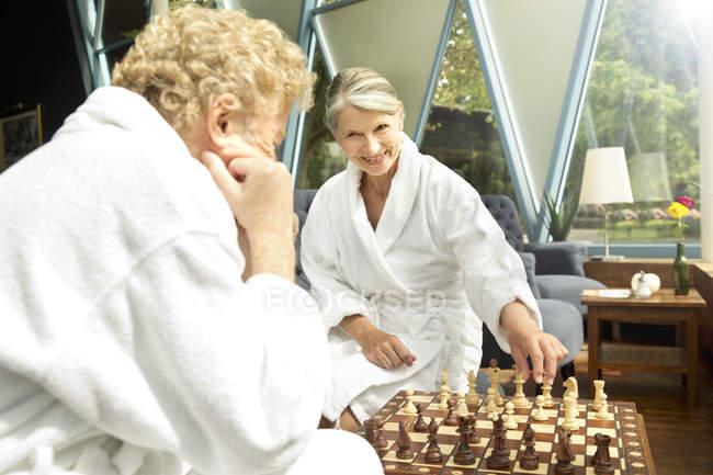 Старшая пара в халатах играет в шахматы — стоковое фото