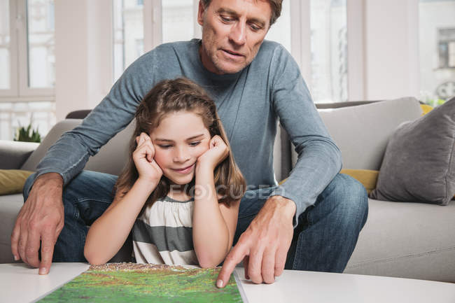 Father and little daughter with map in the living room — Stock Photo