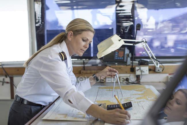 Officier de pont femmes travaillant sur une carte nautique — Photo de stock