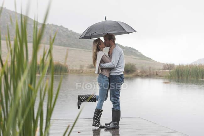 Besos pareja de pie en la lluvia con paraguas — Stock Photo