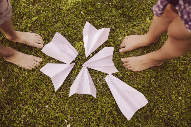 Girl and boy standing with different paper planes in garden — Stock Photo