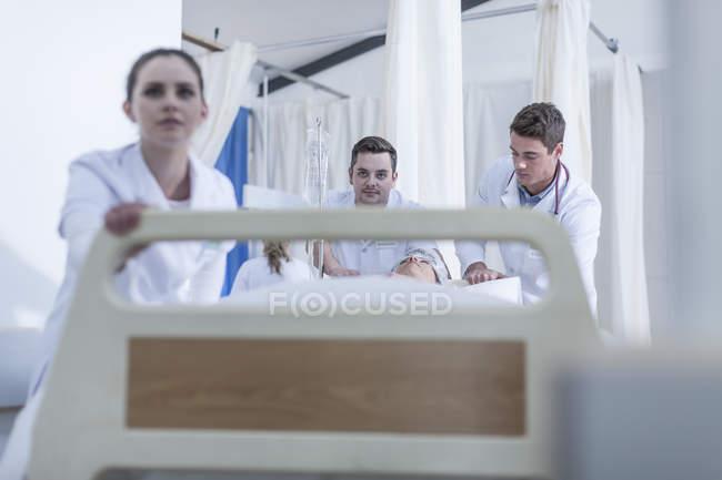 Krankenhauspersonal schubst Bett mit Patient auf Boden — Stockfoto