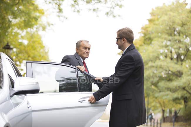 Шофера, відкриваючи двері автомобіля для бізнесмена — стокове фото