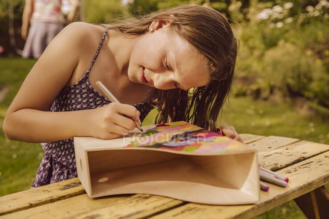 Mädchen zeichnet auf einer hölzernen Magazinmappe im Garten — Stockfoto