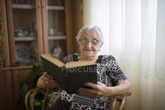 Senior woman reading a book in chair at home — Stock Photo