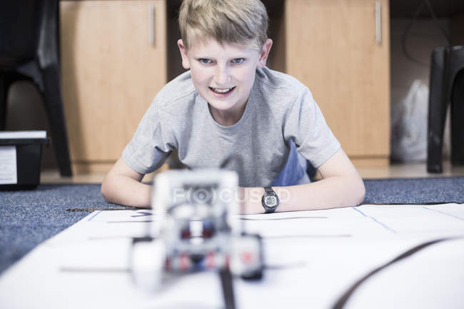 Schoolboy in robotics class testing vehicle on test track — Stock Photo