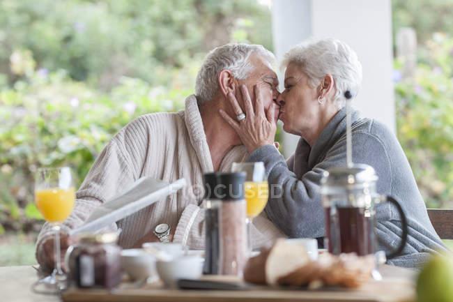 Senior Mann küsst ihren Mann am Frühstückstisch — Stockfoto