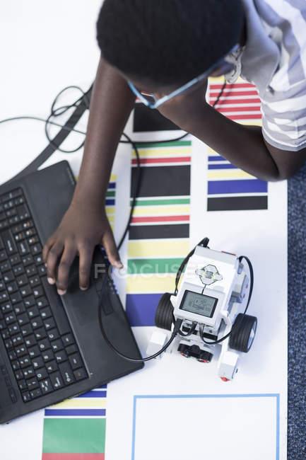 Школяр з ноутбук у класі робототехніки, випробування транспортного засобу на тестуванням на треку — стокове фото