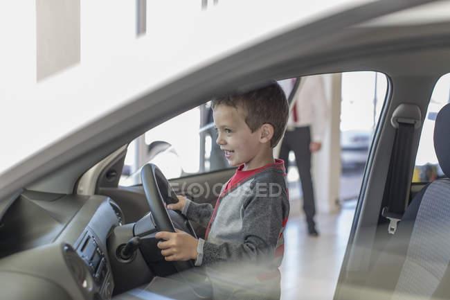 Rapaz feliz no carro revendedor dentro carro direção — Fotografia de Stock