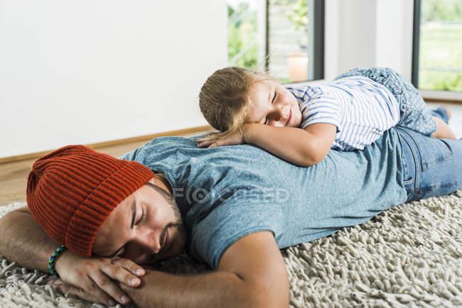 Padre e figlia dormire sul tappeto a casa — Foto stock